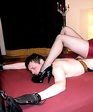Two Mistresses play and torment their slave using a strap-on and heels.